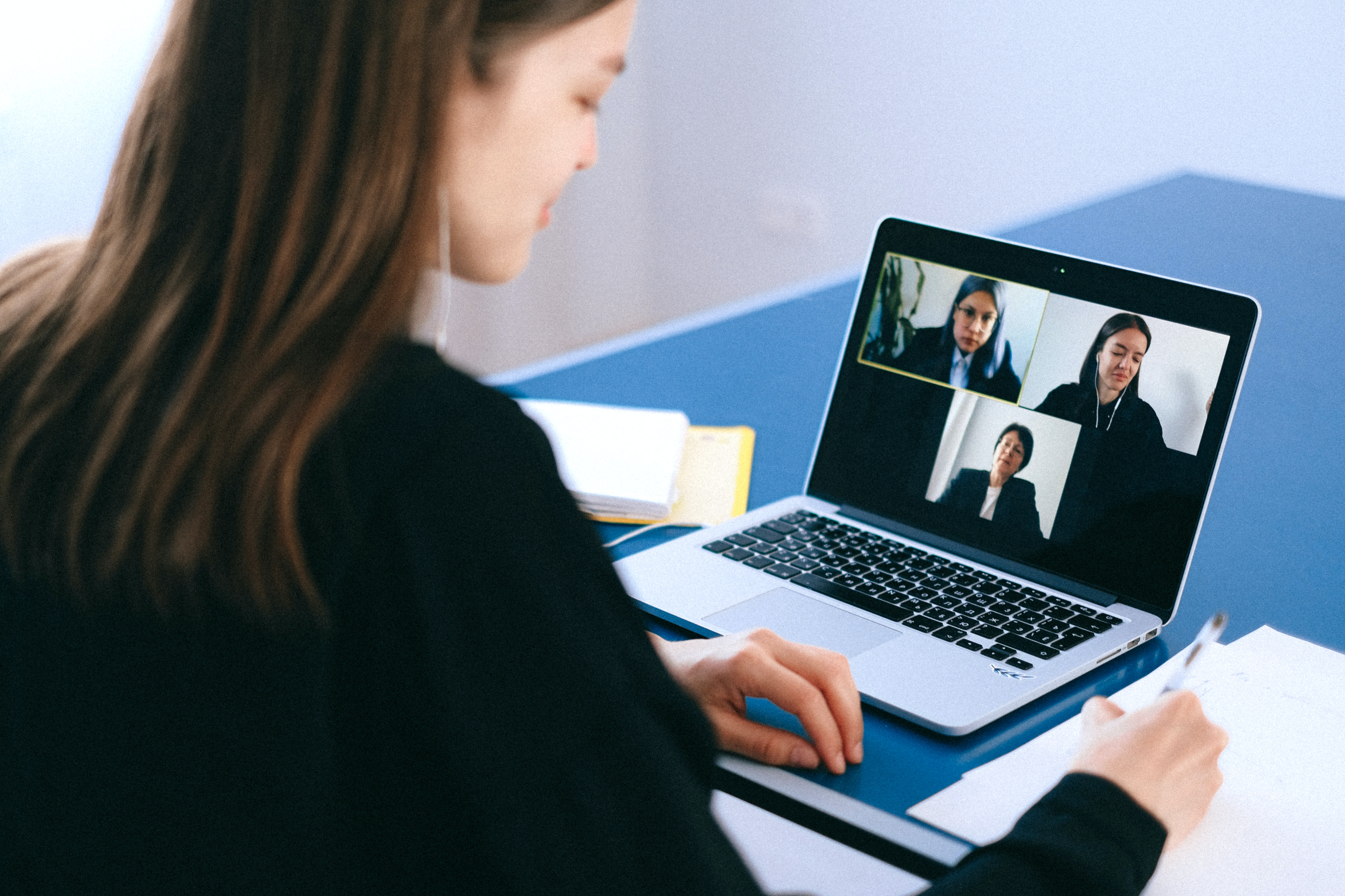 Woman chatting with three other women through a virtual meeting